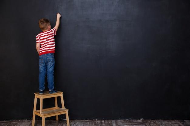 Vista posterior del niño lindo niño escribiendo con tiza