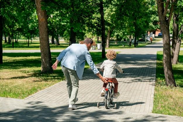 Vista posterior del niño en ropa casual montando bicicleta a lo largo de la carretera en un parque público mientras su padre corre cerca en un día soleado de verano