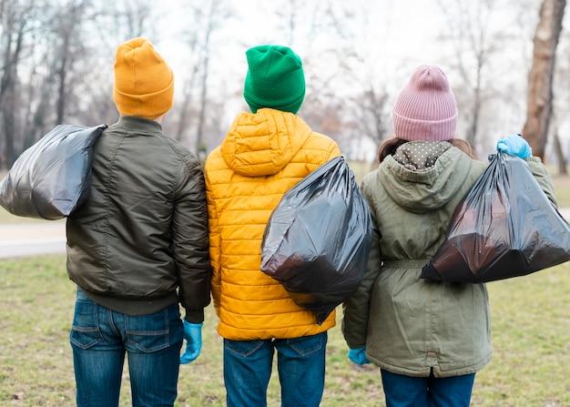 Vista posterior de niños con bolsas de plástico en la espalda