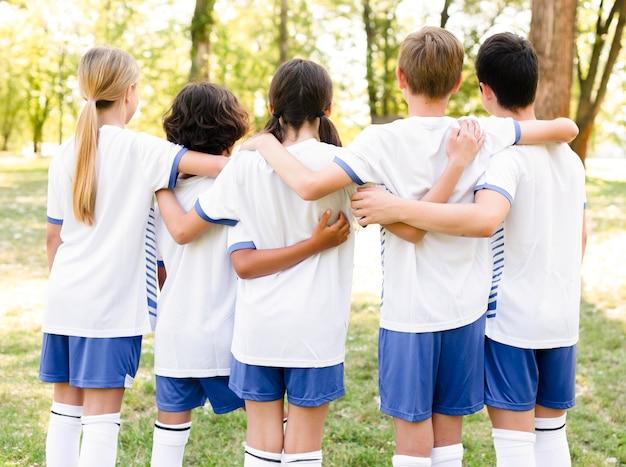 Vista posterior de los niños en ropa deportiva abrazados