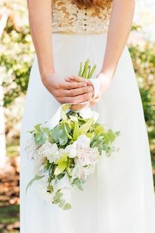 Vista posterior de una novia con la mano detrás de su espalda sosteniendo un ramo de flores