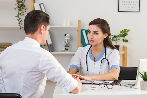 Vista posterior paciente hablando con doctora