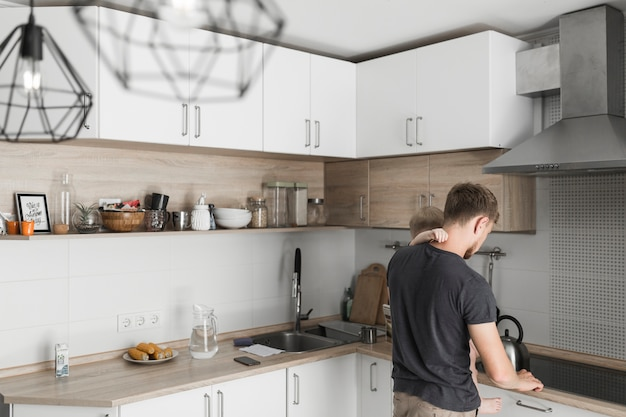 Vista posterior de un padre cargando a su hijo trabajando en la cocina.