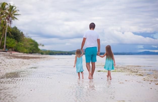 Vista posterior del padre y sus dos hijas caminando junto al mar