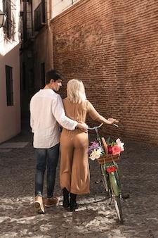 Vista posterior de la pareja abrazada y bicicleta