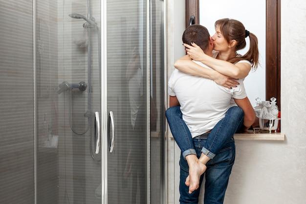 Vista posterior pareja abrazándose y besándose en el baño.