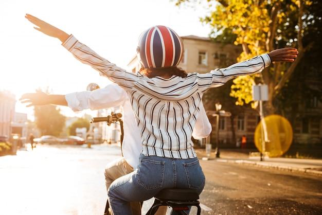 Vista posterior de la pareja africana monta en moto moderna en la calle