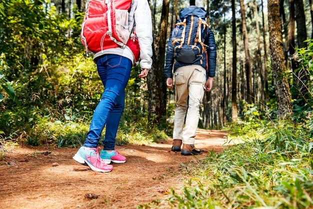 Vista posterior de una pareja de excursionistas asiáticos con mochila caminando hacia abajo
