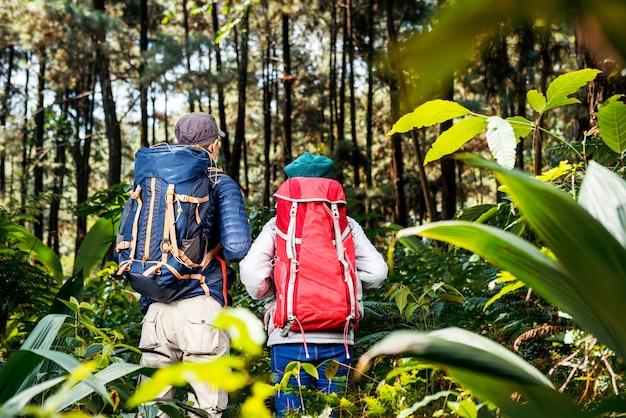 Vista posterior de una pareja de excursionistas asiáticos con mochila explorando