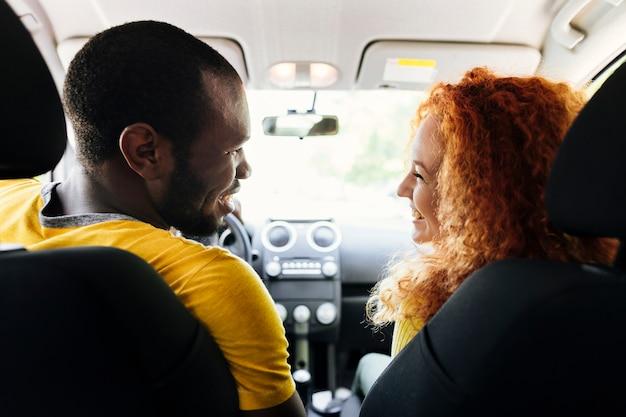 Vista posterior de una pareja interracial en un carro.
