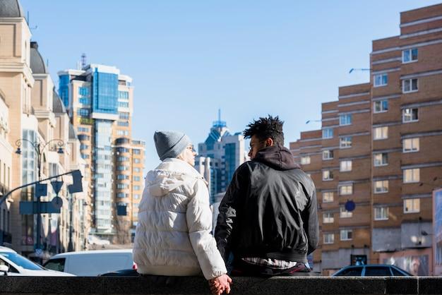 Vista posterior de la pareja interracial joven sentada en la calle frente a los edificios de la ciudad