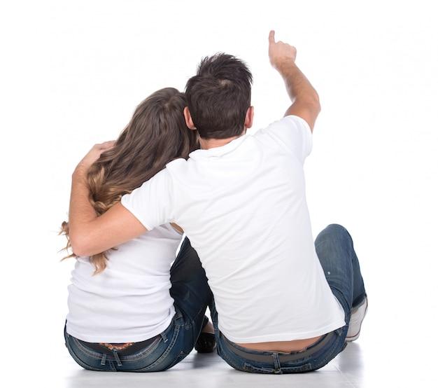 La vista posterior de la pareja joven se sienta en la tierra detrás.