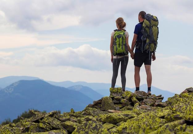 Vista posterior de la pareja de jóvenes turistas con mochilas