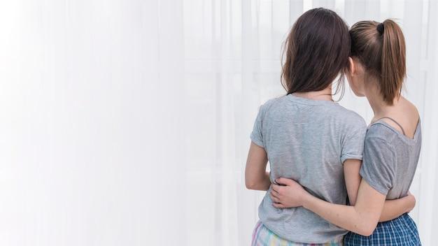 Vista posterior de la pareja de lesbianas jóvenes abrazando mirando la cortina blanca