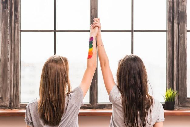 Vista posterior de la pareja de lesbianas jóvenes tomándose las manos de cada uno de pie frente a la ventana