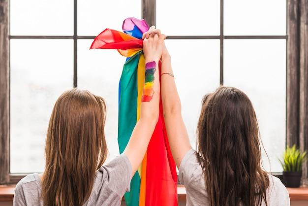 Vista posterior de una pareja de lesbianas sosteniendo las manos y la bandera del arco iris mirando la ventana