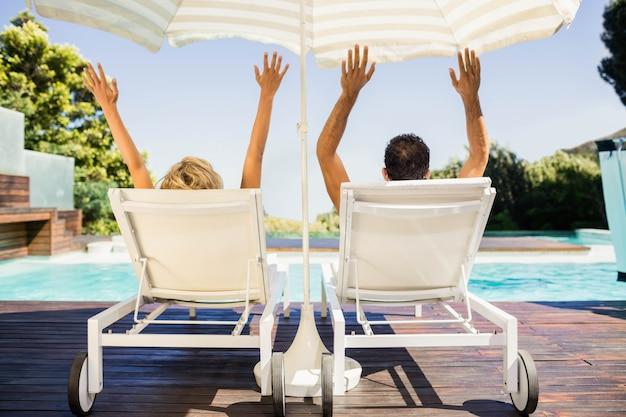Vista posterior de la pareja levantando las manos y acostado en las tumbonas junto a la piscina