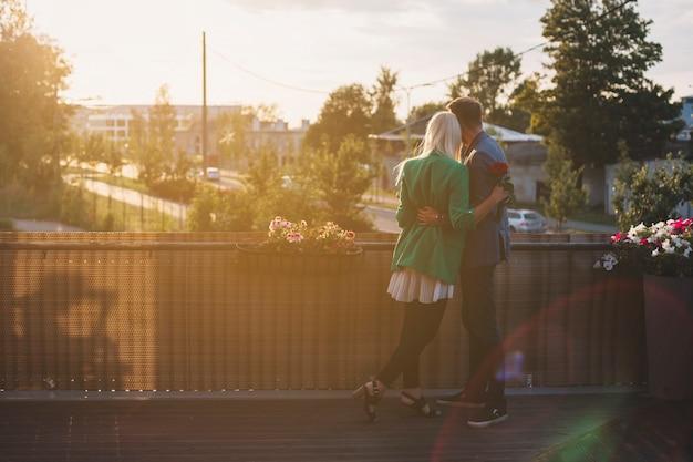 Vista posterior de la pareja de pie en el balcón mirando a otro lado