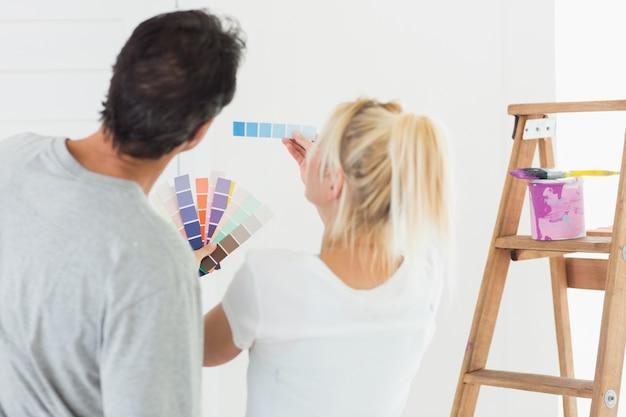 Vista posterior de una pareja que elige el color para pintar una habitación