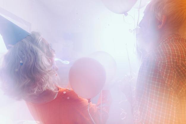 Vista posterior de una pareja senior que sopla la burbuja de jabón con una varita en la habitación llena de humo