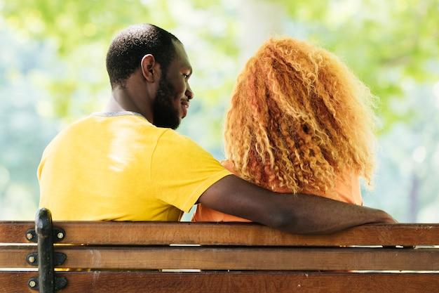 Vista posterior de la pareja sentada en un banco
