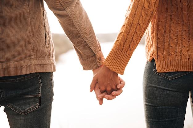 Vista posterior pareja tomados de la mano