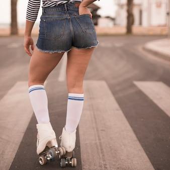 Vista posterior de una patinadora con la mano en el bolsillo de pie en la carretera