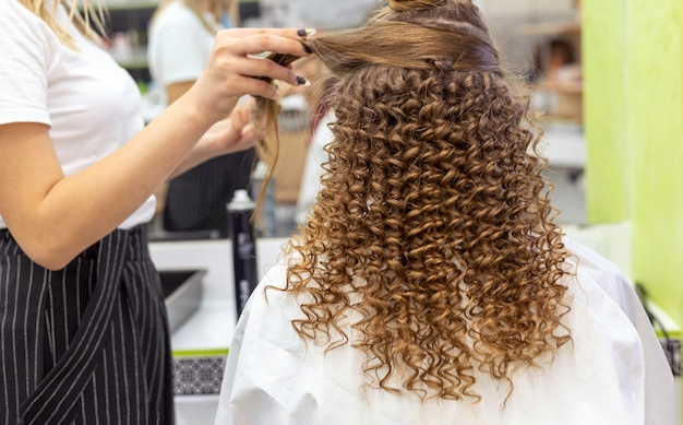 Vista posterior del peinado. peluquería haciendo peinado a mujer de cabello rubio rojo con cabello largo en salón de belleza