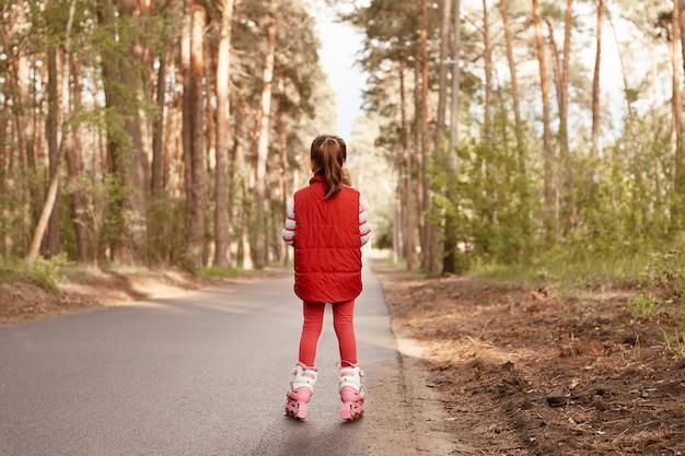 Vista posterior de la pequeña mujer encantadora con chaqueta informal roja y leggins, montando patines, posando al revés, jugando en el bosque y disfrutando de la hermosa naturaleza