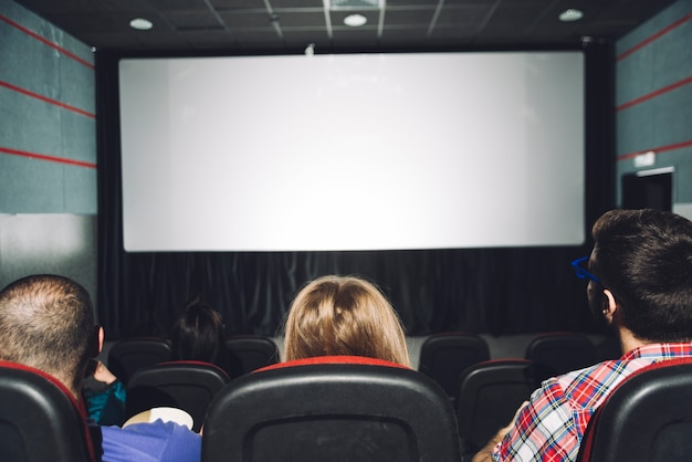 Vista posterior personas mirando la pantalla de cine