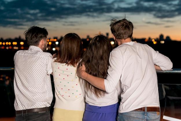 Vista posterior de las personas que buscan en la distancia