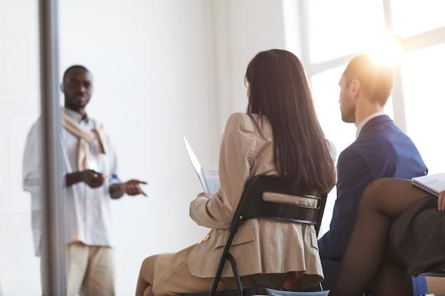 Vista posterior de las personas que escuchan al entrenador de negocios mientras están sentados en sillas en la audiencia en una conferencia o seminario, destello de lente, espacio de copia