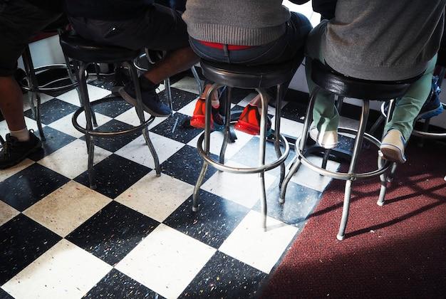 Vista posterior de personas sentadas en un taburete de bar.
