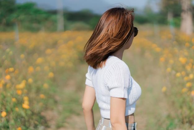 Vista posterior de pie rubia joven en vestido blanco feliz disfrutando el verano en campo amarillo en el jardín
