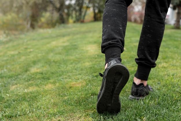Vista posterior de las piernas del hombre caminando sobre la hierba