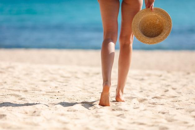 Vista posterior de las piernas de la mujer delgada de pie en la playa de arena