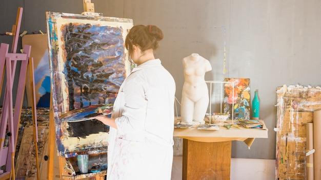Vista posterior de la pintura profesional del artista en el taller.