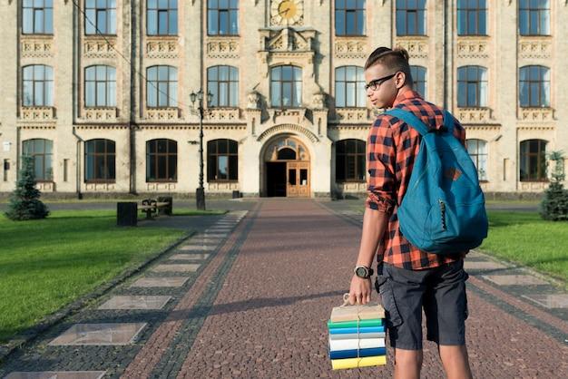 Vista posterior plano medio de un estudiante de secundaria mirando hacia los lados.