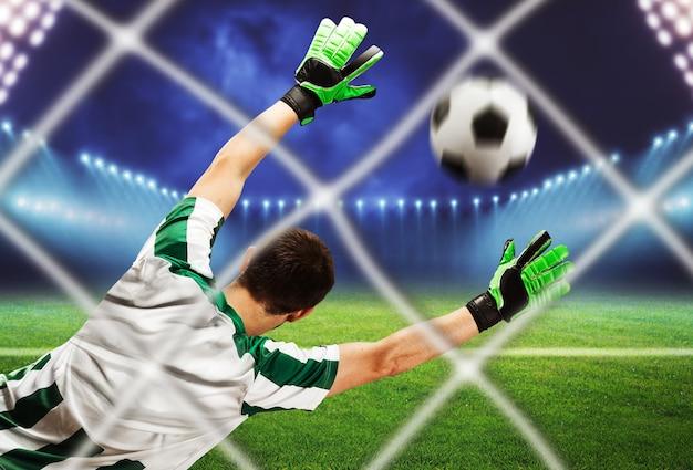 Vista posterior del portero atrapando el balón en el campo de fútbol
