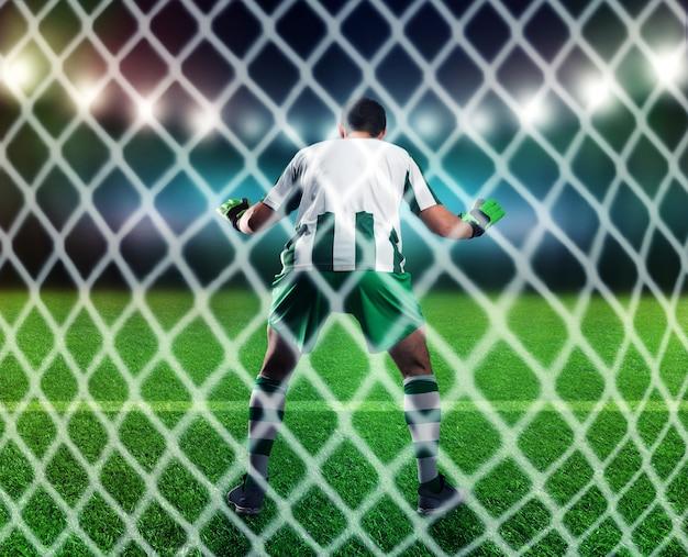 Vista posterior del portero está atrapando la pelota en el campo de fútbol.