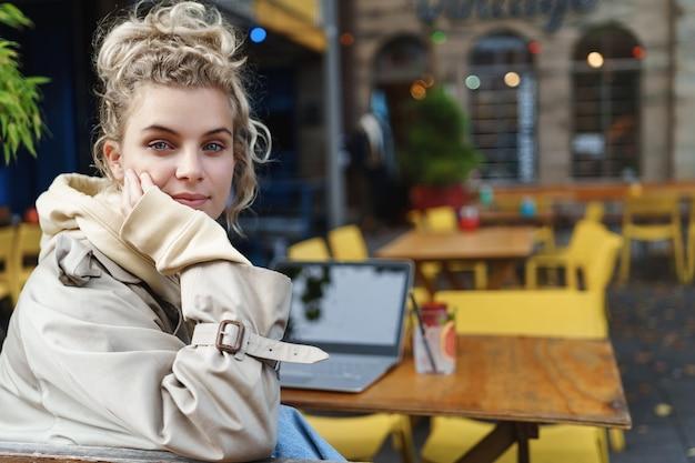 Vista posterior de primer plano de la hermosa chica rubia se vuelve a la cámara mientras está sentado mesa de café con computadora portátil y cóctel.