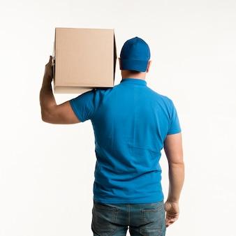 Vista posterior del repartidor llevando una caja de cartón