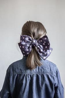 Vista posterior, retrato de una colegiala con un hermoso lazo de lunares azul en el pelo.