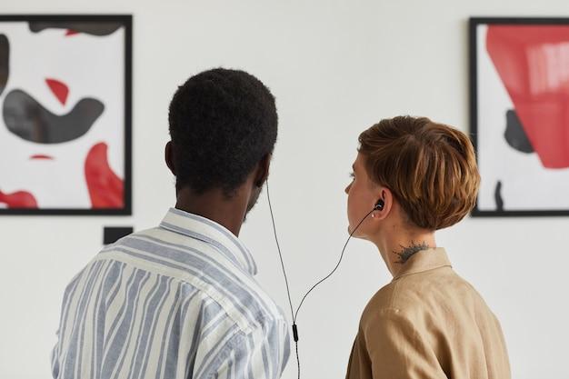 Vista posterior retrato de dos jóvenes mirando pinturas y compartiendo audioguías mientras exploran la exposición de la galería de arte moderno,