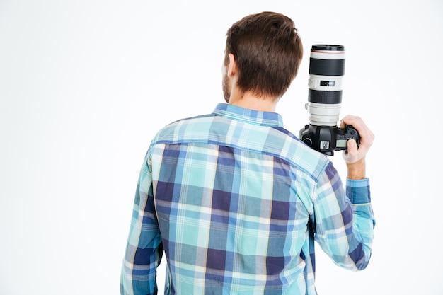 Vista posterior retrato de un fotógrafo masculino sosteniendo una cámara de fotos aislado sobre un fondo blanco.