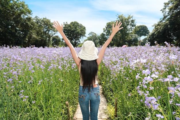 Vista posterior retrato de mujer hermosa divirtiéndose y disfrutando entre flores naga-crested field en la naturaleza