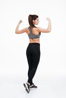 Vista posterior retrato de una mujer joven fitness de pie y mostrando sus bíceps aislado