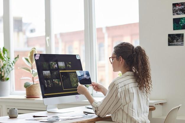 Vista posterior retrato de mujer joven moderna sosteniendo fotografías revisando para su publicación mientras trabaja en la pc en la oficina blanca, espacio de copia