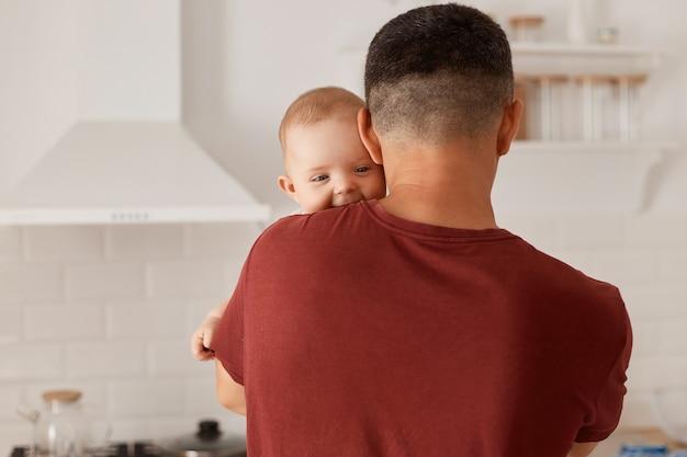 Vista posterior retrato de padre joven adulto de raza caucásica con hijo o hija, lindo bebé mirando a cámara sobre el hombro del hombre, posando interior con cocina en segundo plano.