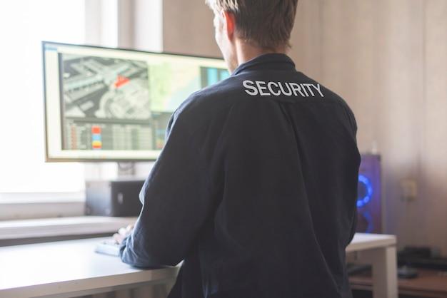 Una vista posterior de la seguridad masculina se sienta frente a la computadora y verifica la cámara de circuito cerrado de televisión en línea